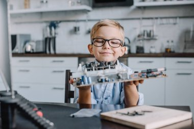 adorable boy holding motherboard at table at home