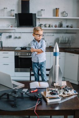 adorable boy standing with crossed arms and looking at rocket model in kitchen on weekend