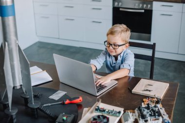 high angle view of boy using laptop at table with rocket model in kitchen on weekend