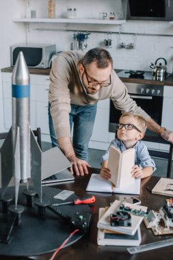 father and son modeling rocket and looking at each other at home