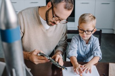 father and son repairing microcircuit together at home