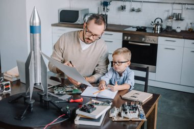 father and son modeling rocket and looking at blueprint at table in kitchen