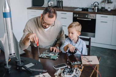 father and son repairing circuit board together at home