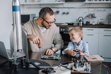 cheerful father and son repairing circuit board and looking at each other at home