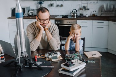 pensive father and son looking at circuit board on table at home