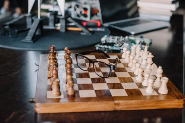 wooden chess board with glasses on table in living room