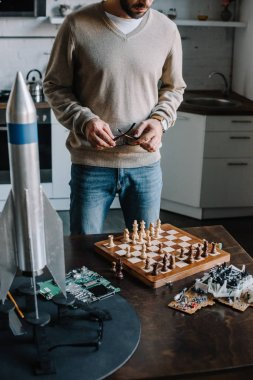 cropped image of man standing near table with chess board at home