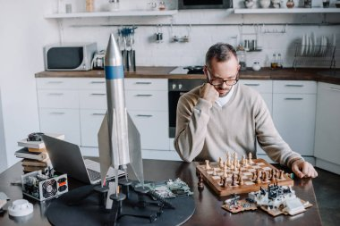 pensive handsome man looking at chess board at home