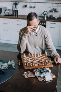 high angle view of tired man playing chess and touching nose bridge at home
