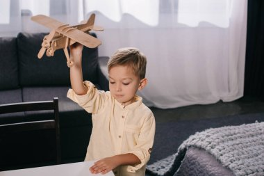 high angle view of adorable child playing with wooden plane model at home