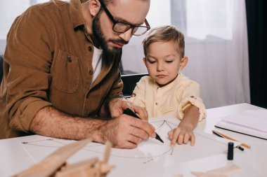 focused father and little son modeling together at home