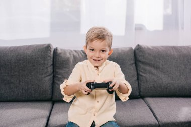 Happy little boy playing with joystick at home stock vector