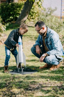 happy father and son playing with model rocket together at sunny day
