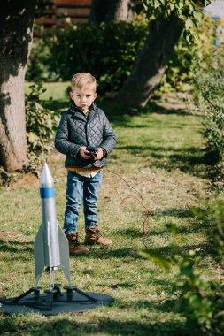 Cute little boy launching model rocket outdoor stock vector