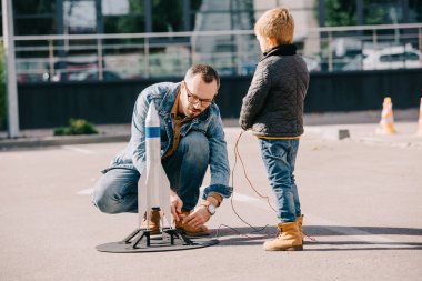 father and little son launching model rocket together outdoor