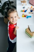 Fotografie vysoký úhel pohled dítěte stojícího na povrchu s knihami a barevné bloky doma