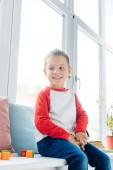 portrét roztomilý veselý chlapce, který seděl u okna doma