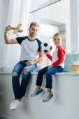 Photo smiling boy with football ball and father with wooden toy plane at home