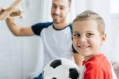 Selektivní fokus usměvavý chlapec s míčem fotbal a otce s dřevěná hračka letadlo doma
