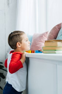 side view of child standing at surface with books and colorful blocks at home
