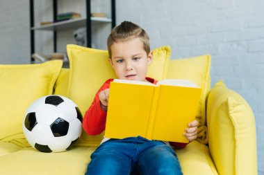 portrait of little boy reading book on yellow sofa with football ball near by at home