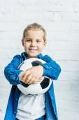 šťastné dítě s fotbalový míč při pohledu na fotoaparát přední bílá cihlová zeď