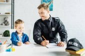 Fotografie smiling young father in police uniform and son drawing together at home