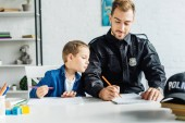 handsome young father in police uniform and son drawing together at home