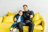 Fényképek csinos fiatal apa, a rendőrségi egységes tévénézés fia otthon sárga kanapén ülve