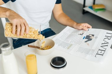 partial view of man having breakfast in kitchen at home