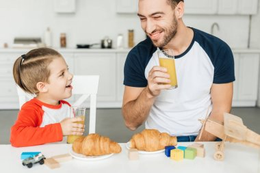 handsome young father and son having breakfast with croissants and orange juice together at home