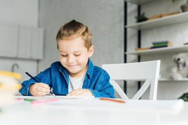 Smiling little child drawing with color pencils at home stock vector
