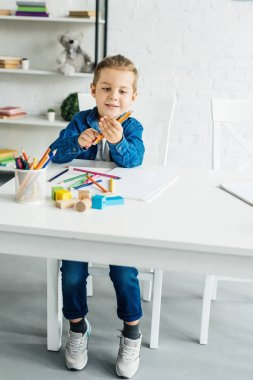 happy little child drawing with color pencils at home