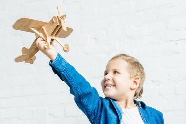 Smiling little kid playing with wooden toy airplane in front of white brick wall stock vector