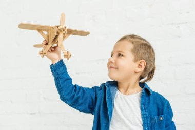 Happy little kid playing with wooden toy airplane in front of white brick wall stock vector