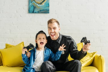 Emotional young father in police uniform and son playing video game while sitting on yellow couch at home stock vector