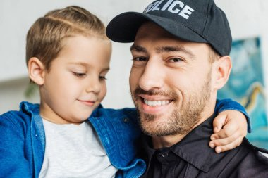 Close-up portrait of happy young father in police uniform carrying his little son and looking at camera stock vector