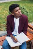 Fotografie bystrý mladý muž sedí na lavičce a psaní v prázdný poznámkového bloku