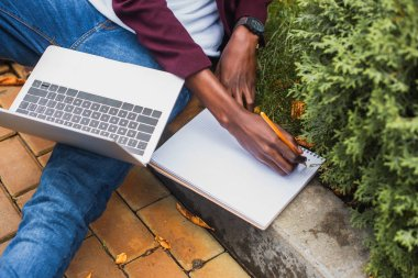 cropped shot of freelancer using laptop and writing in notebook while sitting on curb on street