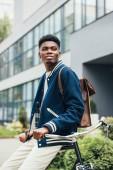 glücklich stilvoll afrikanisch-amerikanischer Mann mit Lederrucksack auf Fahrrad gestützt