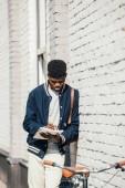 africká americká na volné noze psaní dokumentů a stojící poblíž bílá cihlová zeď