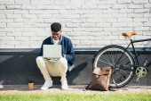 africká americká teleworker pomocí přenosného počítače u kol s kožený batoh a kávu na bílé zdi