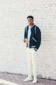 Stylový americký muž, který držel kávu jít blízko bílá cihlová zeď