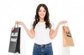 smiling girl holding shopping bags with black friday sale signs isolated on white