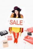 Fényképek gyönyörű lány tartja eladó jele és jelentő közelében bevásárló táska fekete péntek, elszigetelt fehér