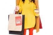 Fotografie verkürzte Ansicht stilvolle Shopaholic mit Kreditkarte und Einkaufstaschen mit Verkauf Tagisolated auf weiß