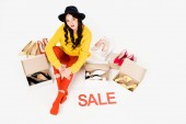Fotografie beautiful shopaholic with sale symbol isolated on white with footwear