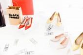 Fotografie zblízka pohled na peníze, ženské boty a nákupní tašky s černým nápisem pátek izolované na bílém