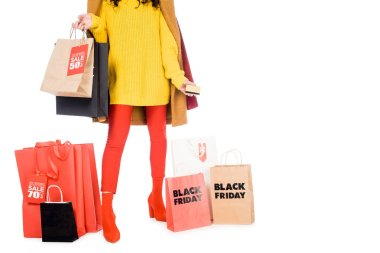 cropped view of girl holding credit card and shopping bags for black friday isolated on white