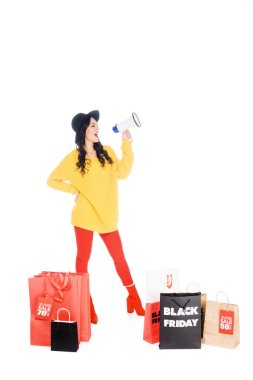 attractive young woman with shopping bags screaming into megaphone for promotion of black friday isolated on white